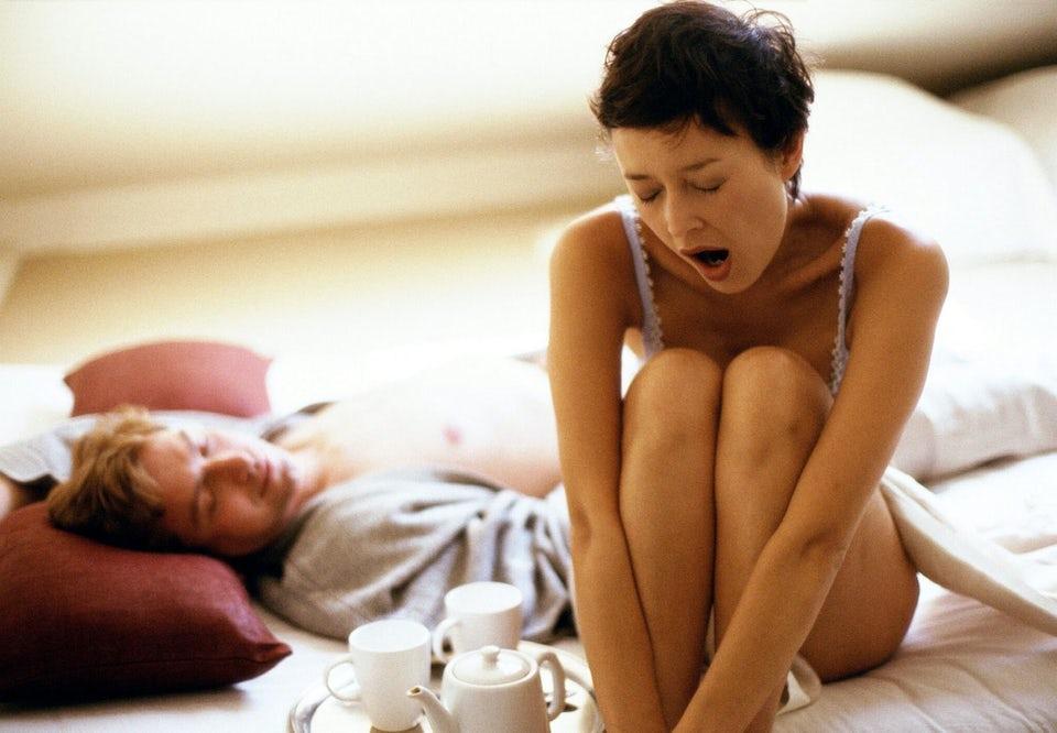 Nainen istuu sängyssä ja haukottelee