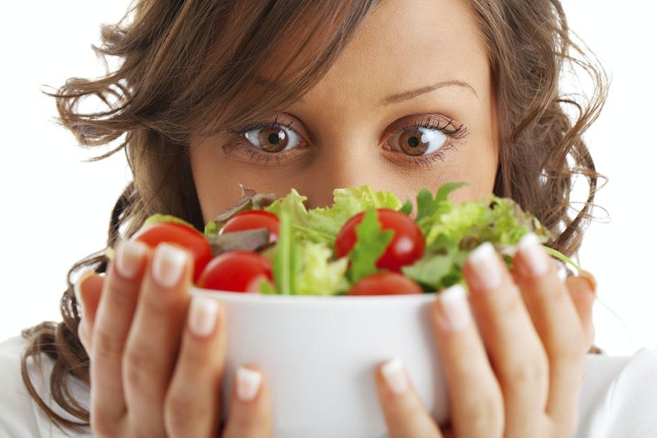 Kvinde kigger på en skål salat med tomater.