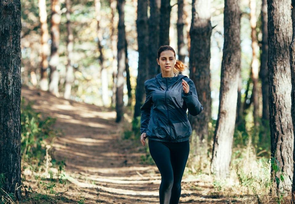 kvinde løber i skov om foråret