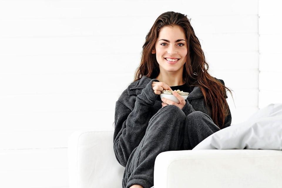 Nainen istuu mukavasti sohvalla