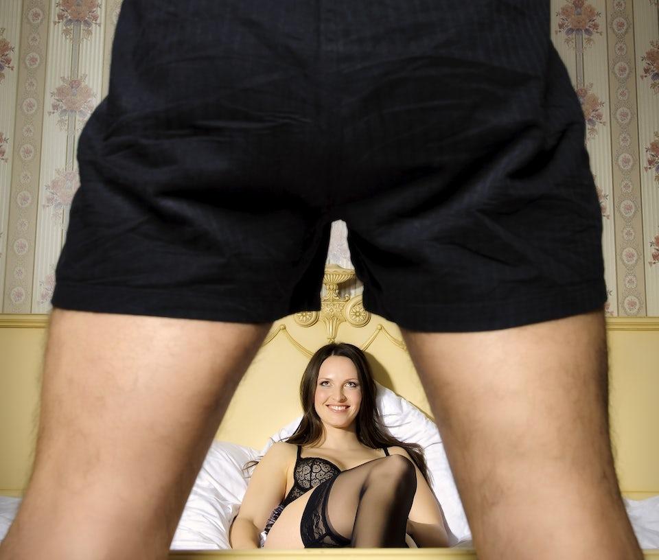 Kvinne iført undertøy ligger i en seng og ser forførende på en mann i bar overkropp.