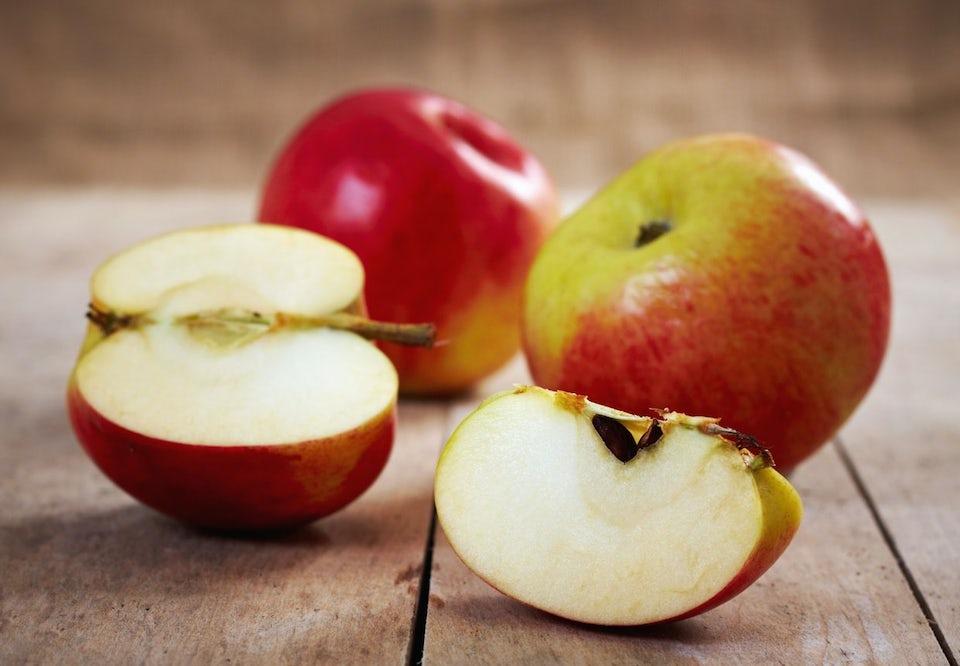 Spröda, röda äpplen på ett träbord