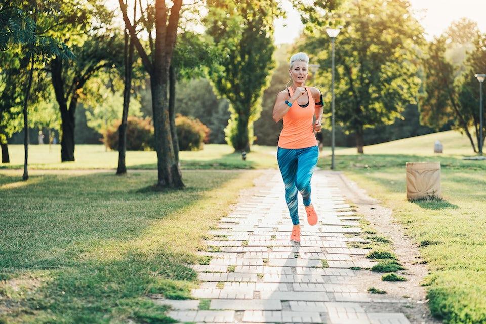 Juoksuasuinen nainen juoksee puistossa