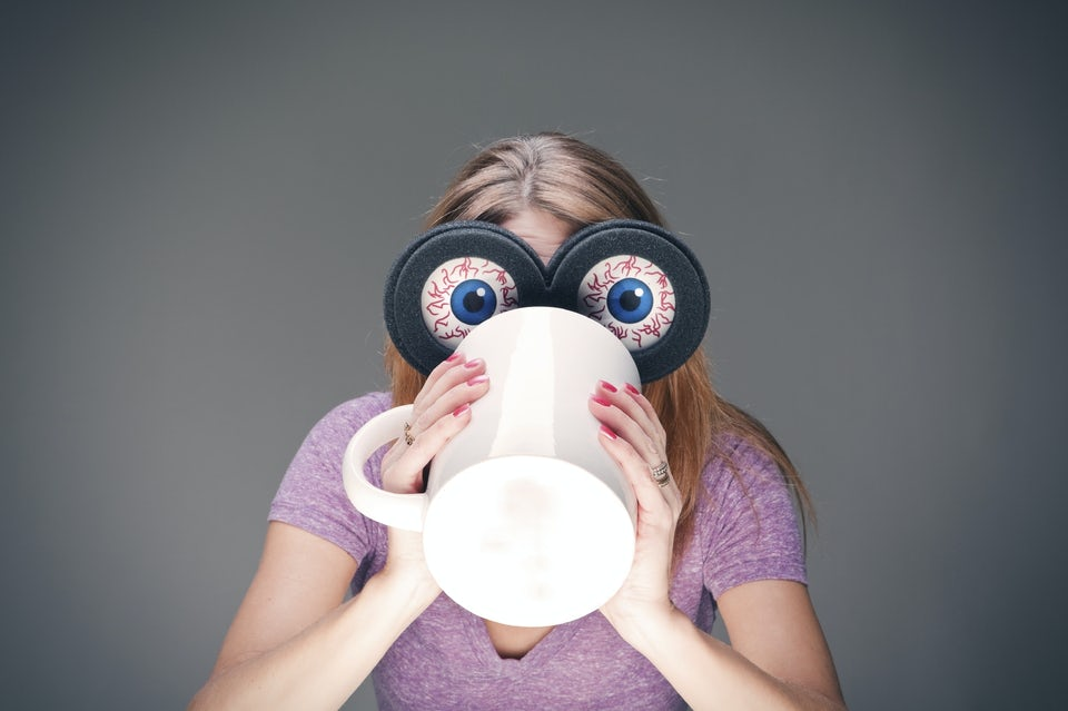 Kvinne med kjempestore og trøtte øyne drikker en stor kopp kaffe.
