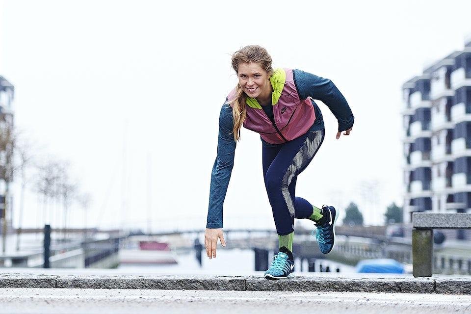 Kvinne løper og trener utendørs mot fortauskant.