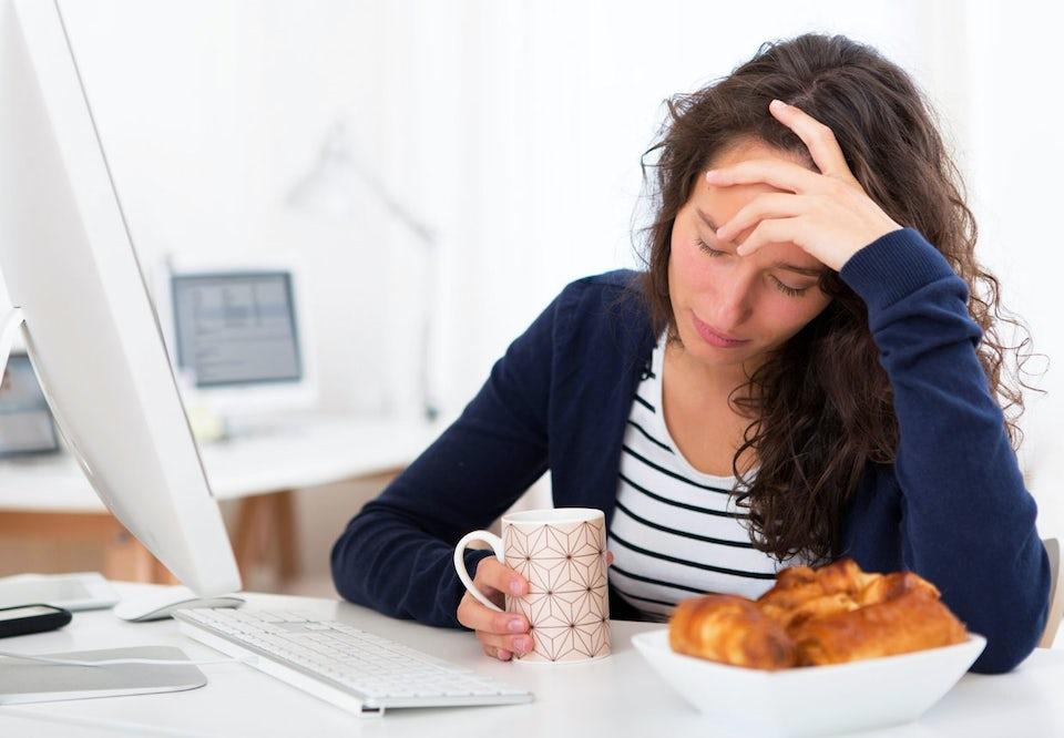 Trøtt kvinne med en kopp kaffe foran pc-en.