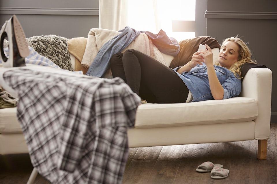 Kvinde i træningstøj sidder afslappet i sofaen med en øl og ser træningsfilm i stedet for at gøre det, som filmen viser.