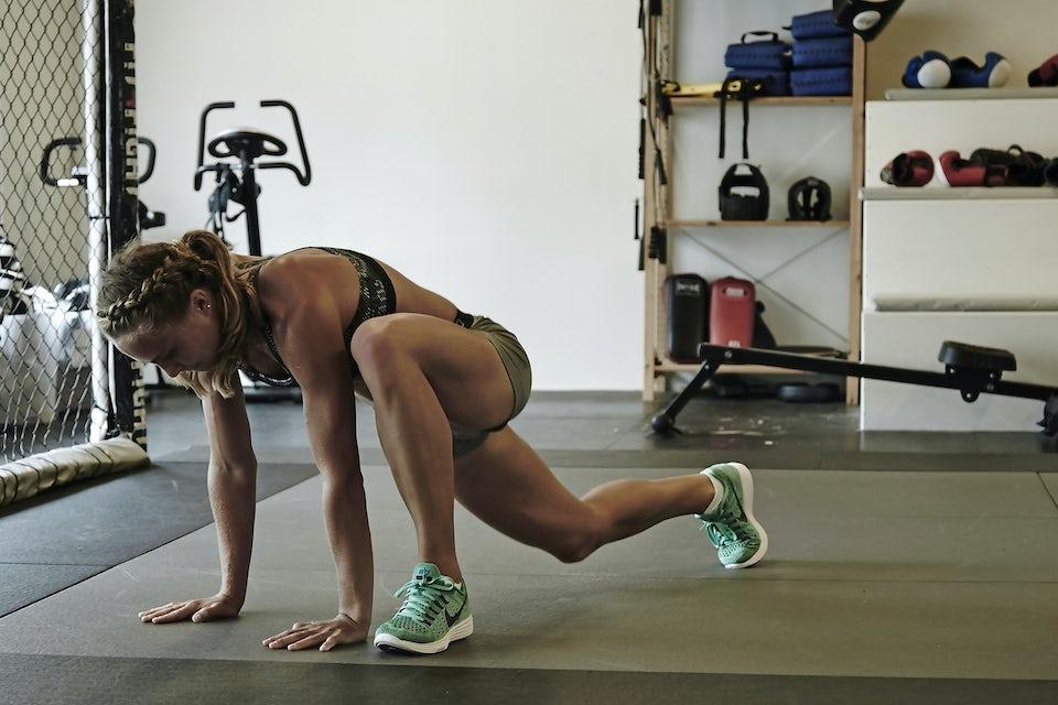 Kvinne gjør mageøvelsen vekslende froskehopp