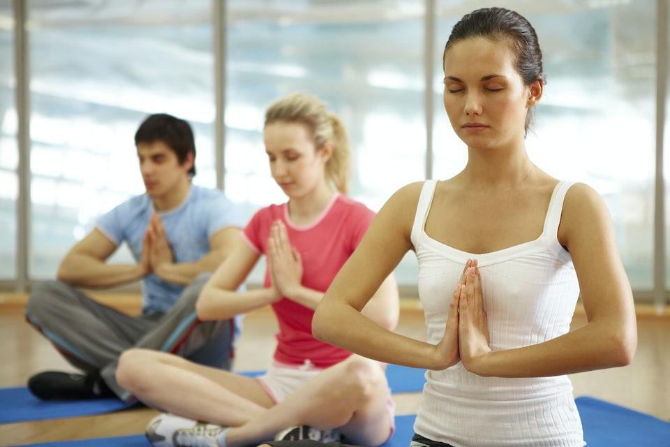 Unga människor mediterar på yogamatta