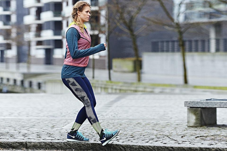 Kvinne trener utendørs på fortauskanten.
