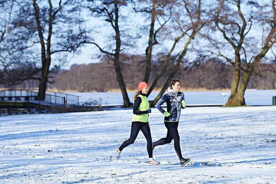 Två kvinnor springer i snön, vinter