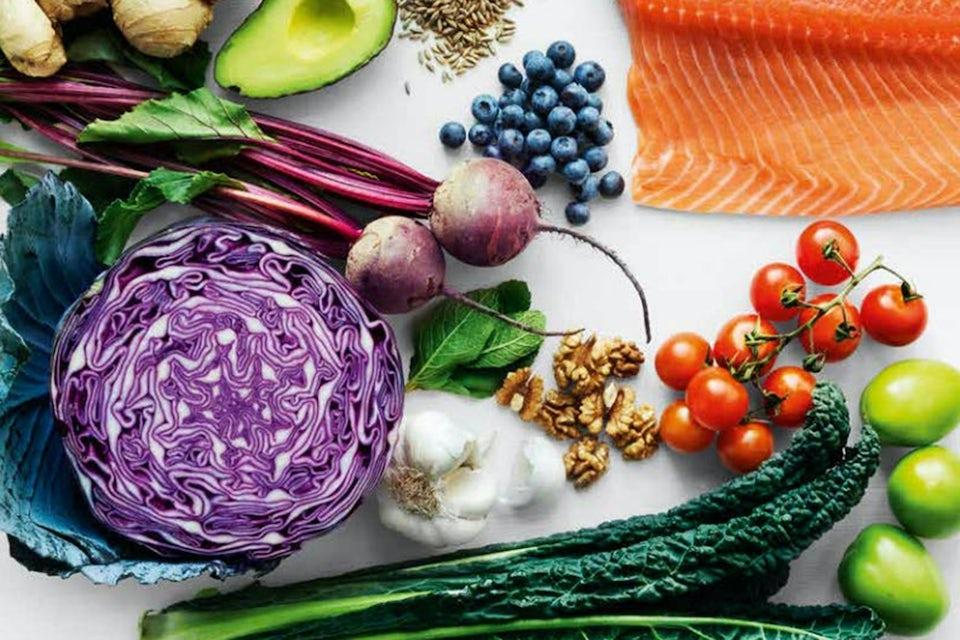 Grøntsager og laks på hvidt bord.