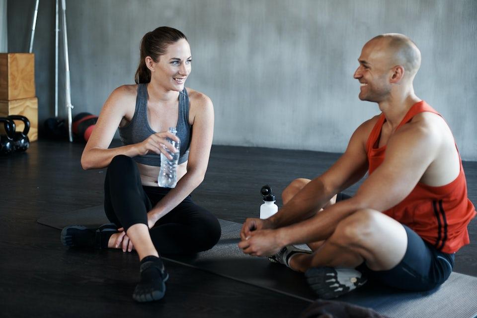 Mand og kvinde sidder på gulv i fitnesscenter og slapper af, smiler