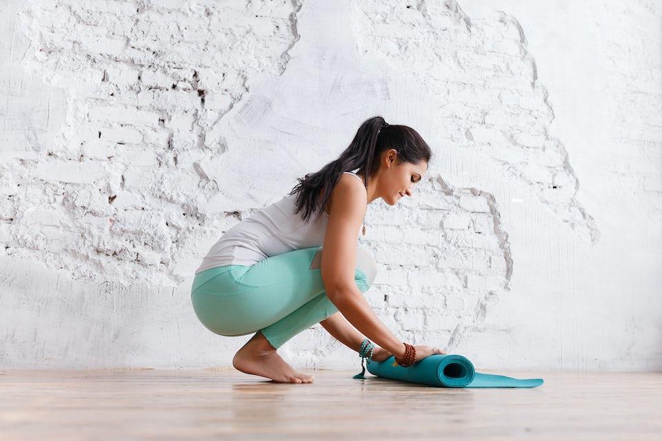 Kvinne rulle sammen matte etter pilates