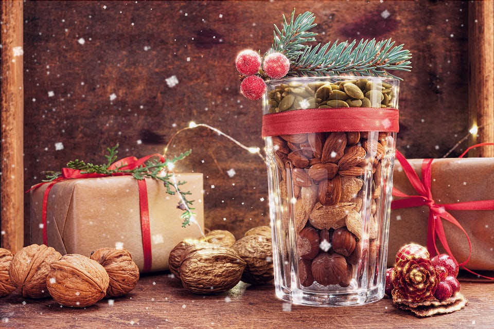 Nainen tonttulakki päässä ja joulupallot käsissä