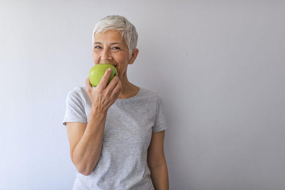 Hymyilevä nainen syö vihreää omenaa