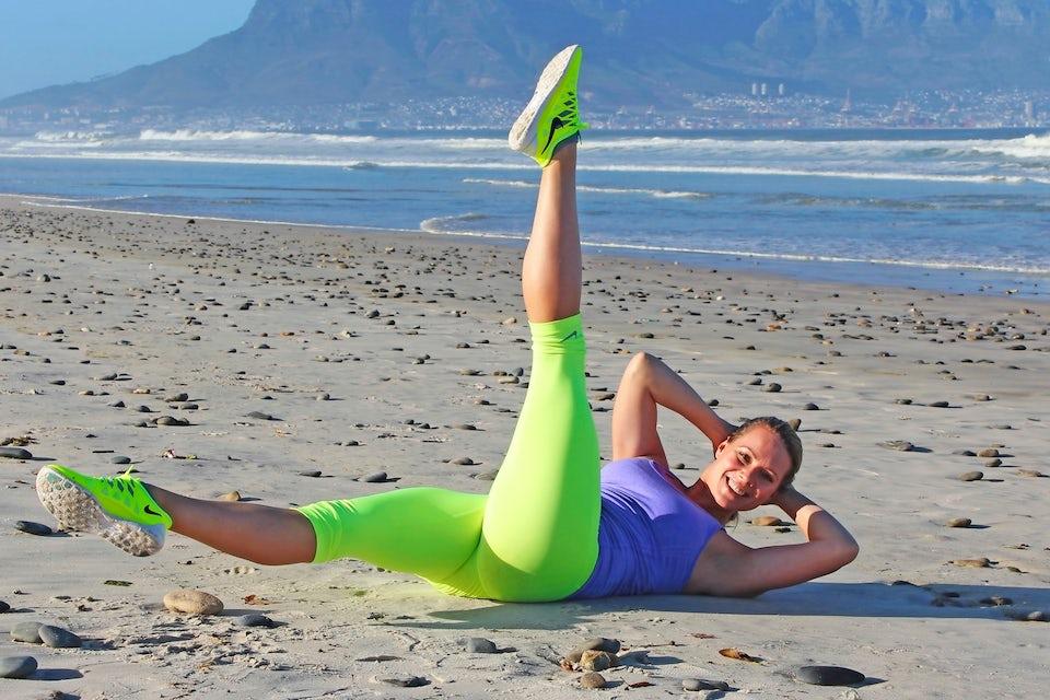 Kvinne trener magen på stranda.