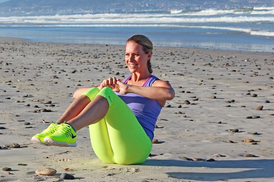 Nainen tekee vatsalihasharjoitetta rannalla