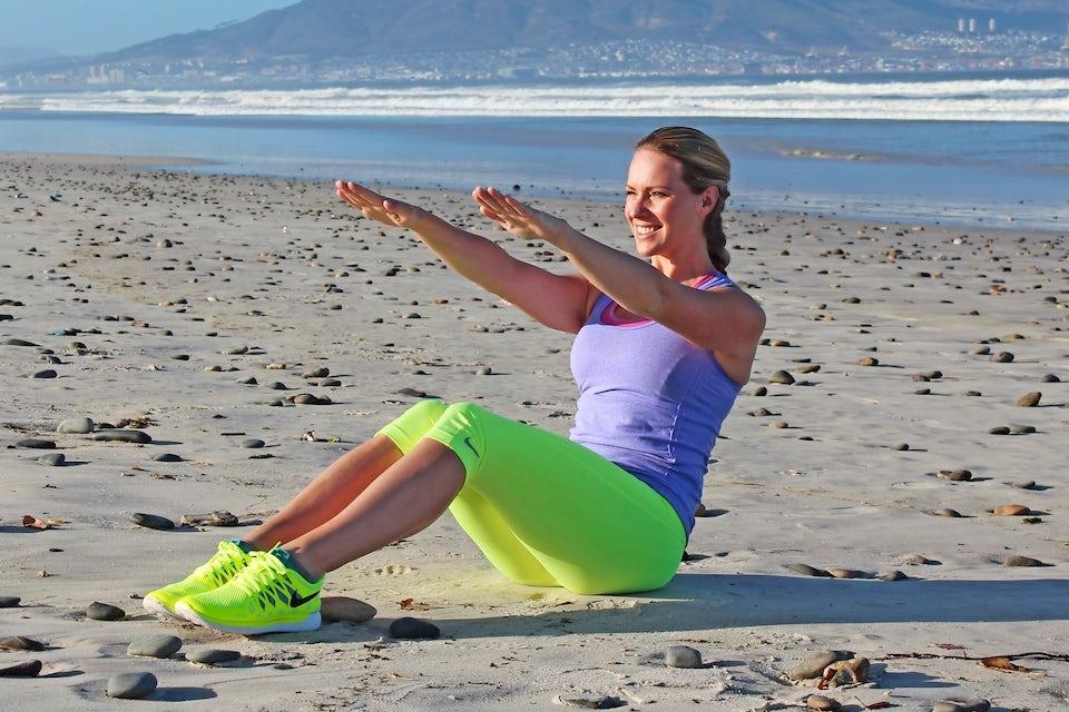 Kvinne trener magen på stranda