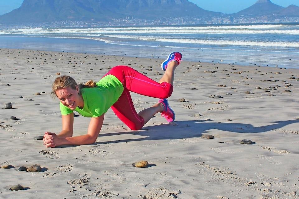 Kvinde træner på en strand.