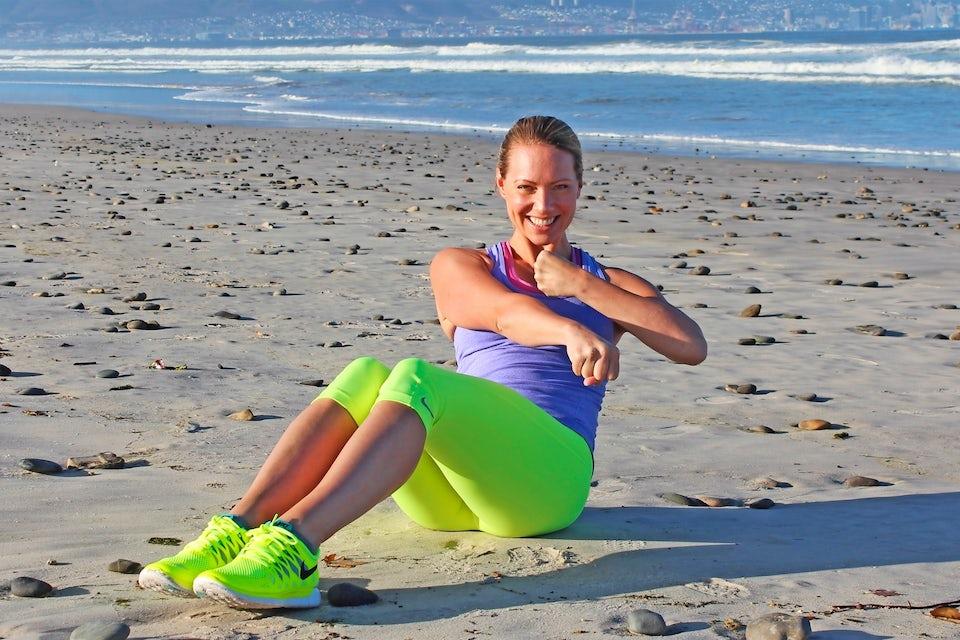 Nainen treenaa rannalla