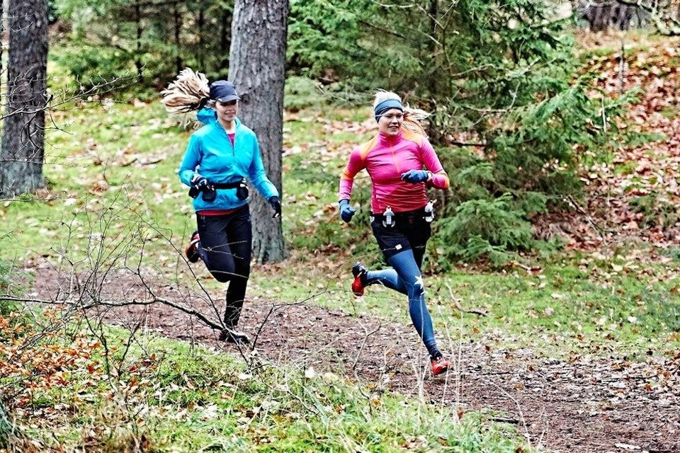 Två kvinnor springer traillöpning i skogen