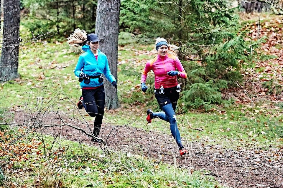 To kvinner trener terrengløping i skogen