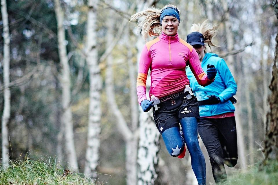 To kvinner trener terrengløping i skogen.