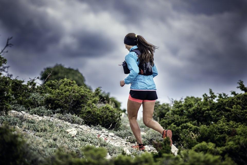 Kvinde løber trailløb op ad bakke
