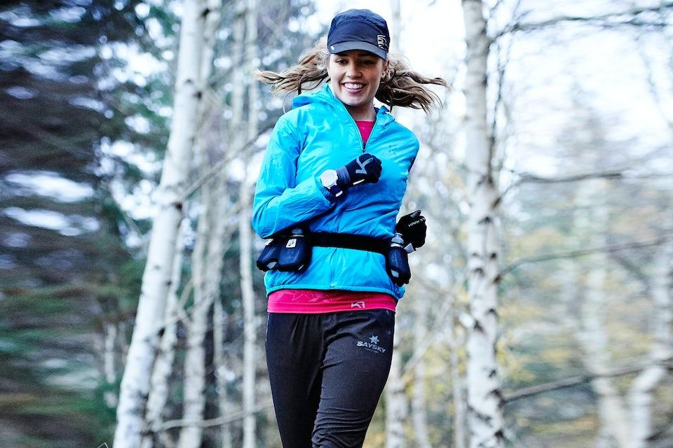 Kvinde løber trailløb i skoven.