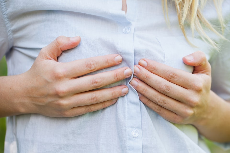 Kvinde med skjorte på holder sig på sine bryster.