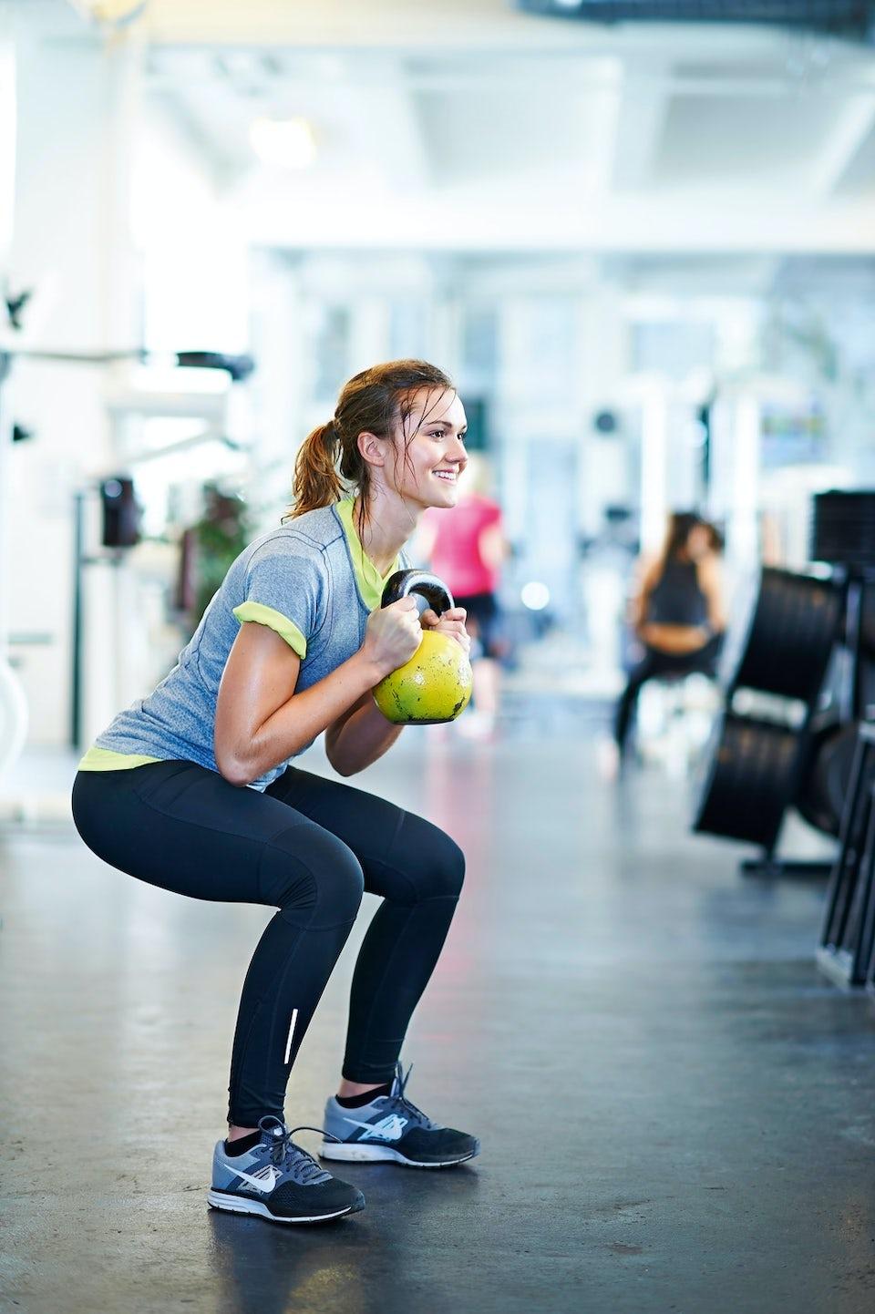 Kvinna gör squats med kettlebell