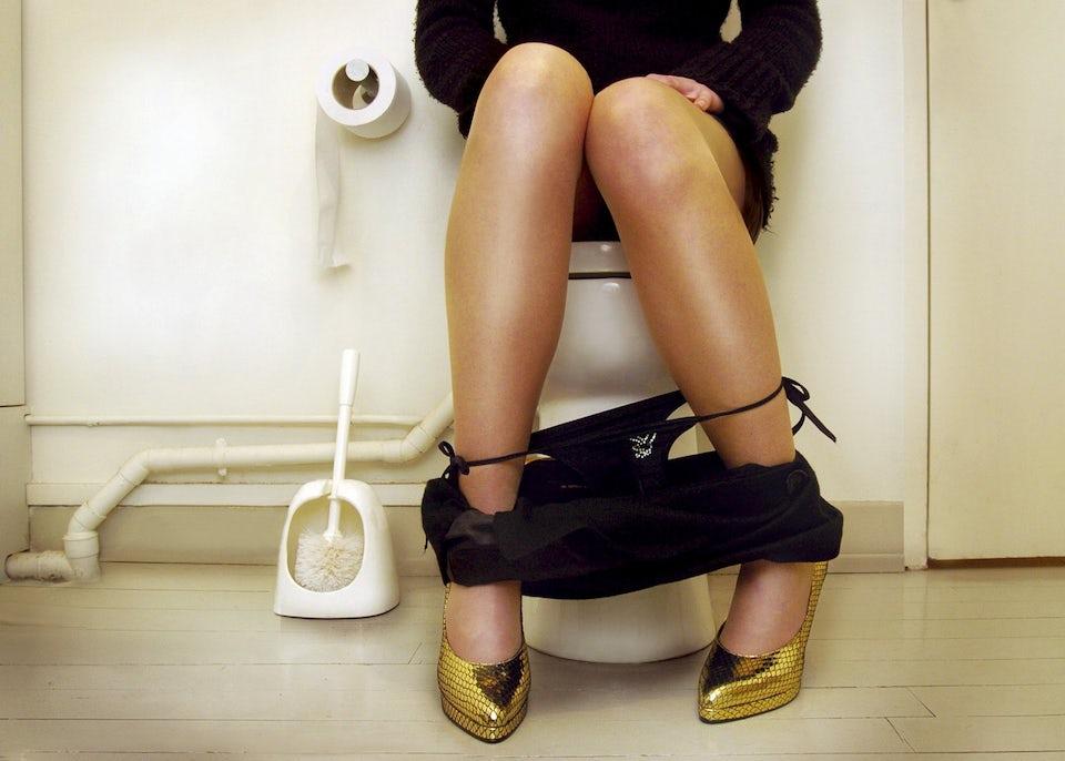 Kvinde på toilet med oppustet mave.