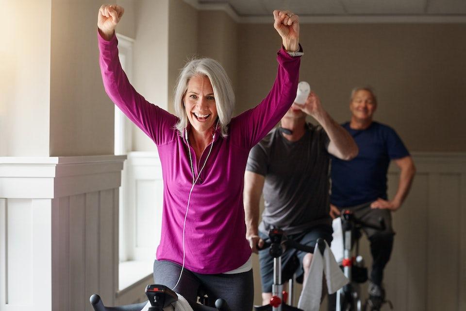 Kvinde på spinningcykel er glad