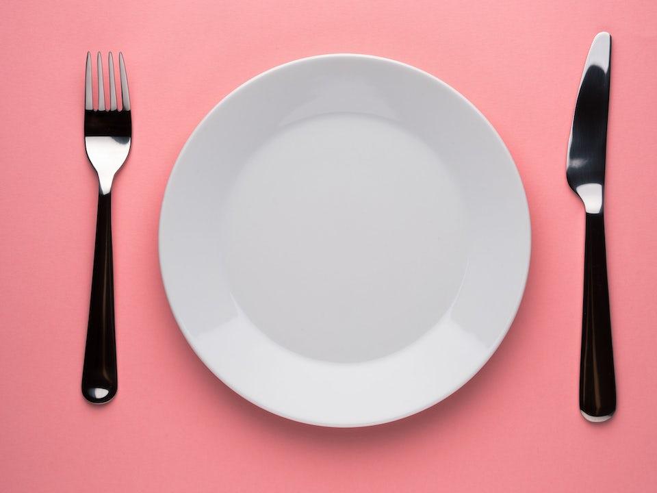 Tyhjä lautanen vaaleanpunaista taustaa vasten