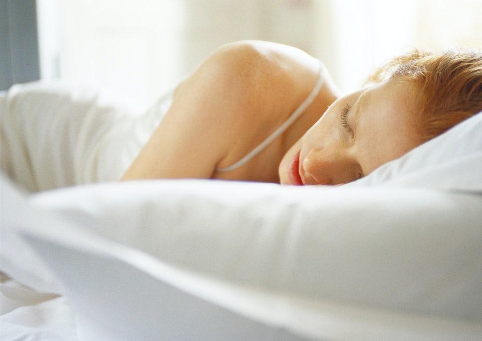 kvinde sover i sin seng