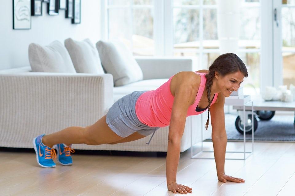 Kvinne er i gang med sirkeltrening på stuegulvet.