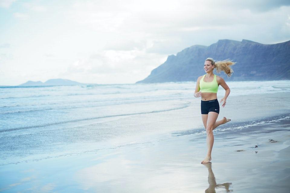 kvinna springer på en strand