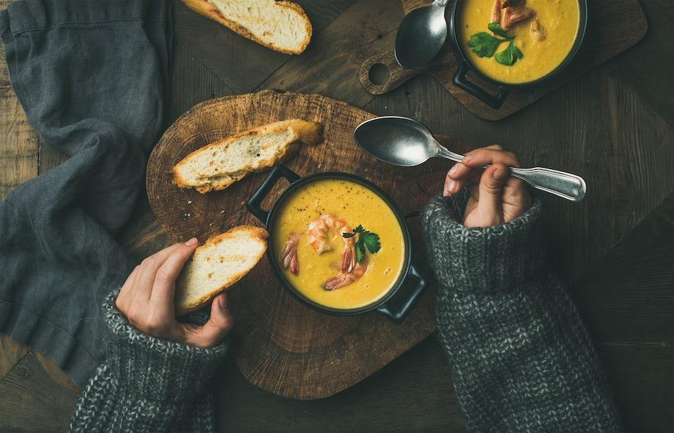 Kvinde spiser grøntsagssuppe med rejer
