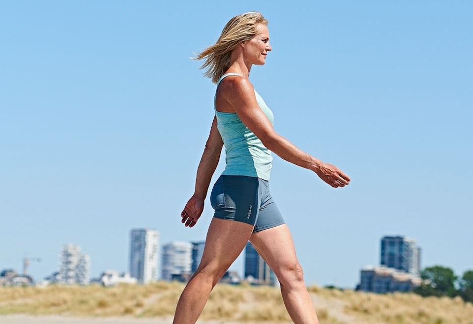 Kvinde der går og træner maven imens