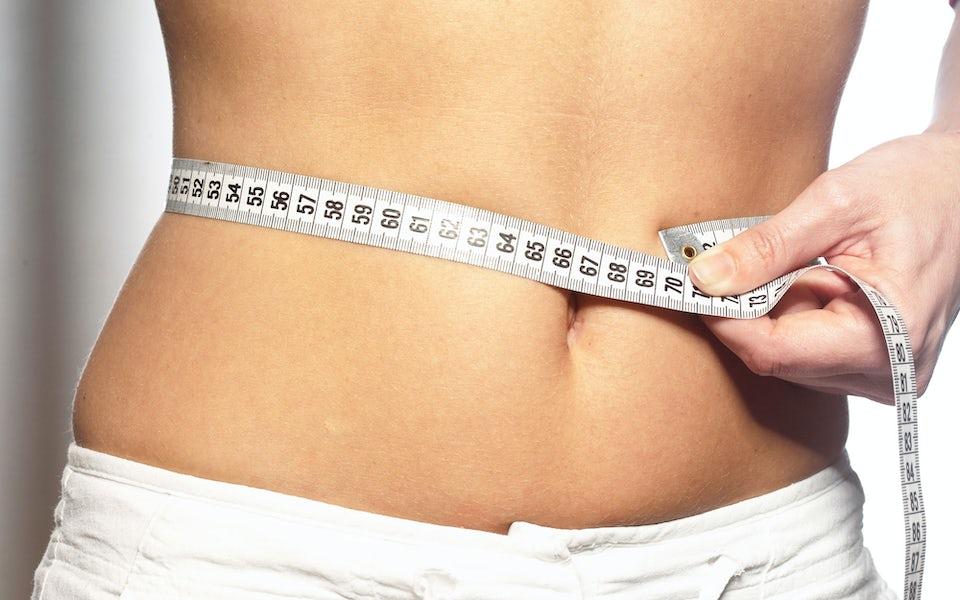 Kvinde måler taljen med målebånd som alternativ til BMI