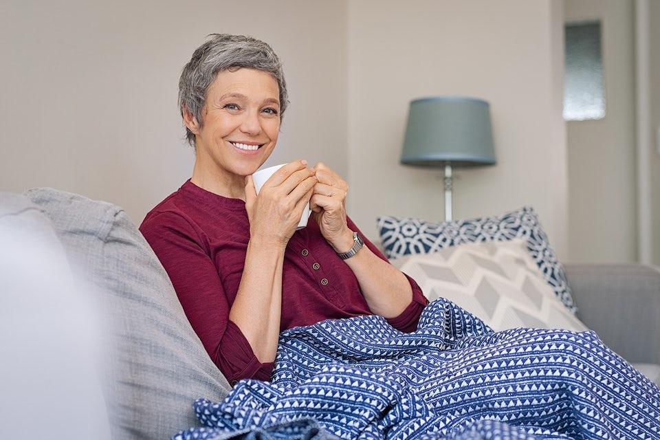 Terve nainen juo teetä sohvalla.