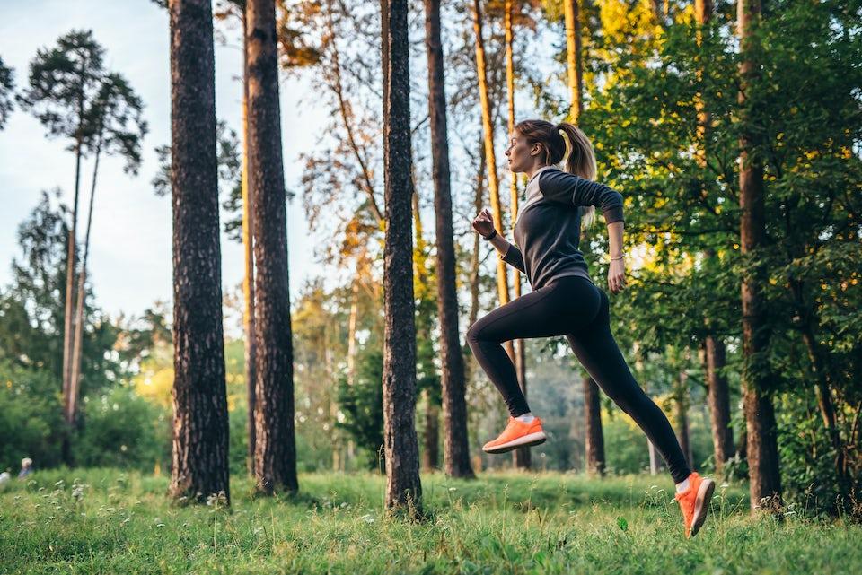 Kvinna springer i skogen