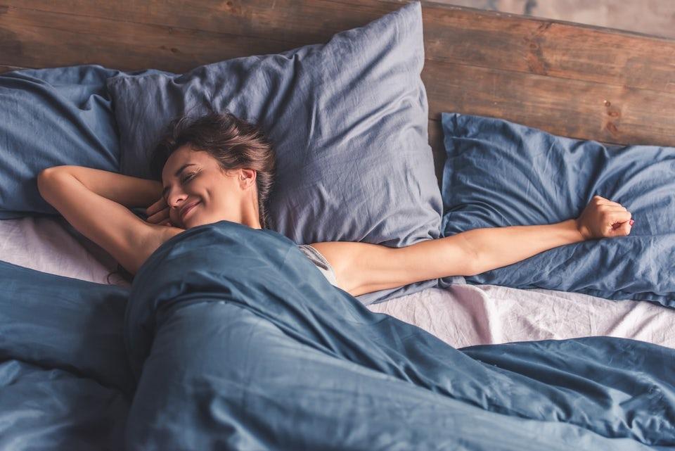 Kvinde ligger i sengen og smiler