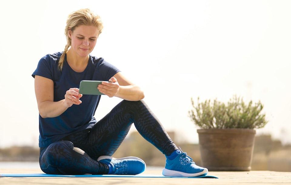 Nainen treenaa ulkona sovelluksen avulla