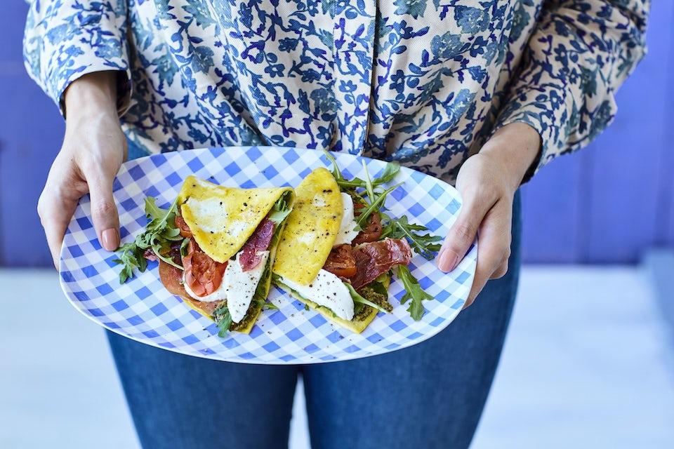Nainen pitelee lautasta, jolla on munakaswrap