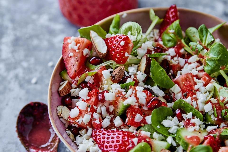Skål med salat av blomkål, jordbær og mandler