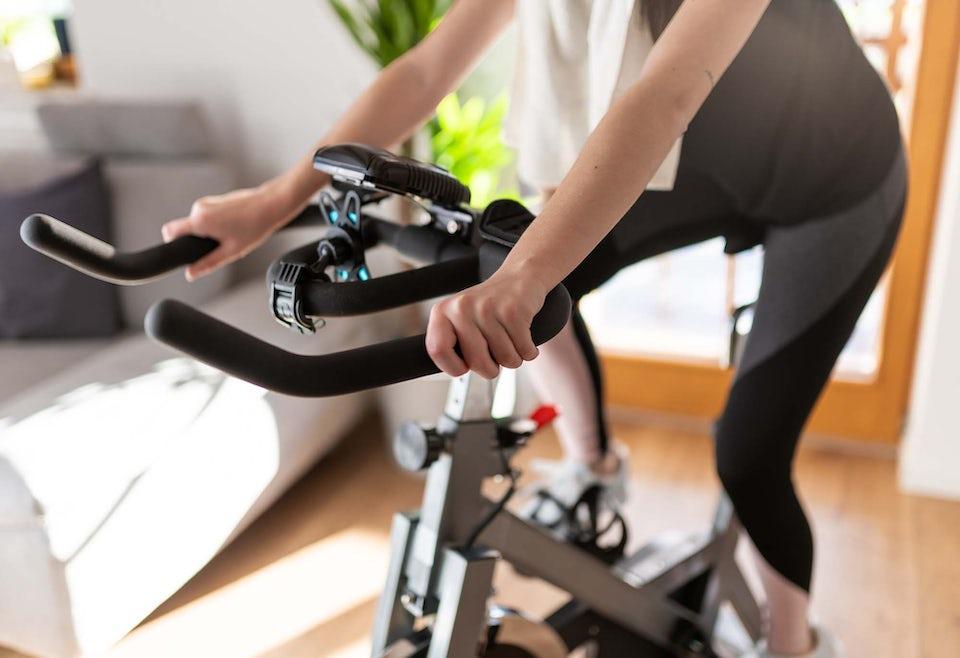 Kvinde træner på motionscykel.