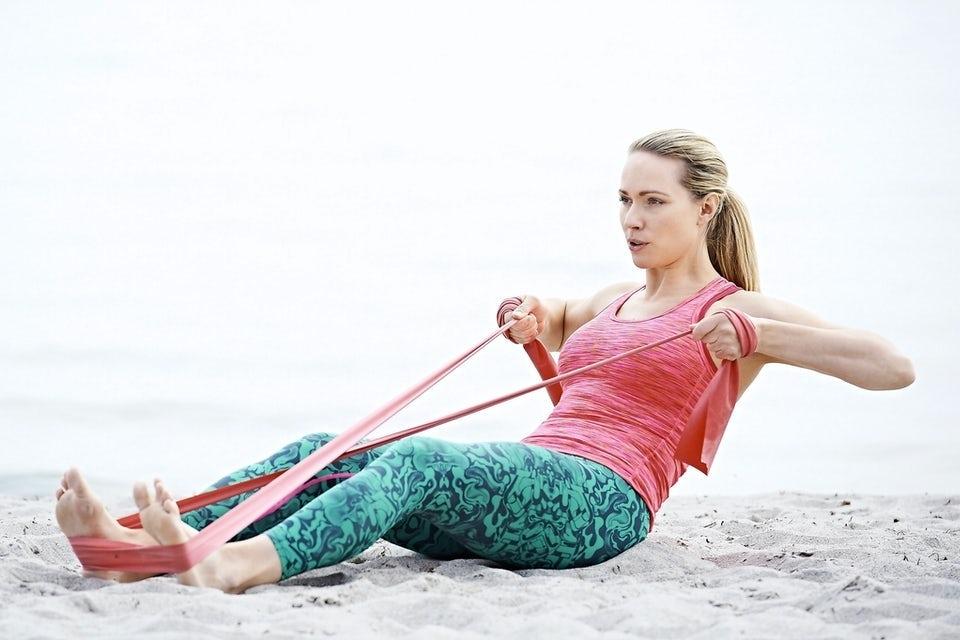 Kvinde laver styrketræning med træningselastik