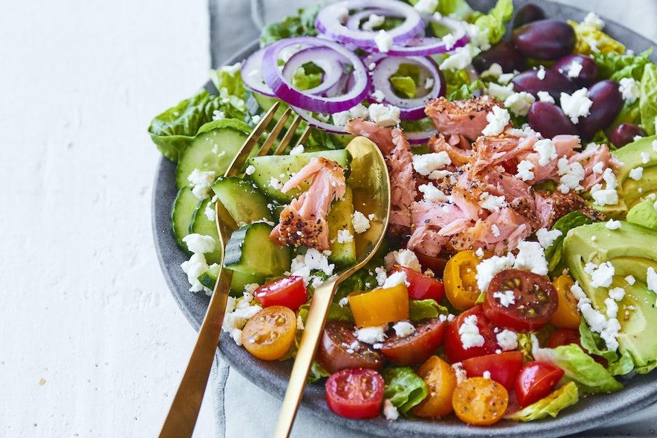 Skål med sallad på lax, avokado, tomat, rödlök, gurka, oliver och fetaost